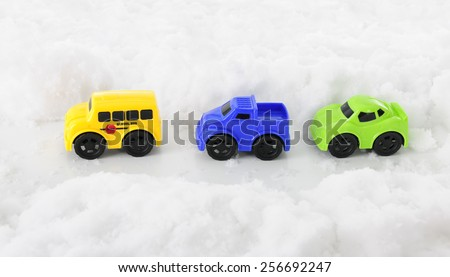 High view of three toy vehicles traveling along a pass through deep snow.  - stock photo