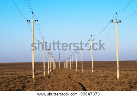 high-voltage columns background (it is photographed at sunset) - stock photo
