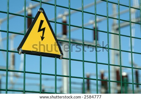 High voltage danger sign in fence of power plant - stock photo