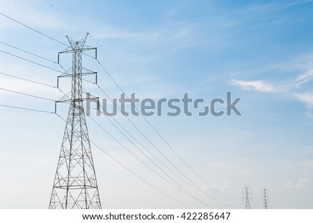 High Voltage Electric Transmission Tower Energy Pylon against the blue sky background. - stock photo