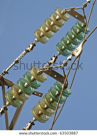 High voltage electrical insulator electric line against the  blue sky. - stock photo