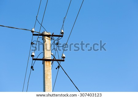 High-voltage electricity pylons against blue sky - stock photo