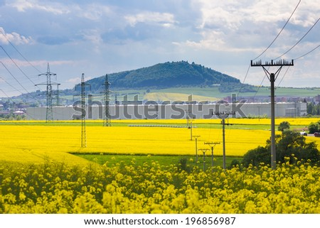 High-voltage electricity pylons in yellow oilseed rape field with small mountains in the background - stock photo