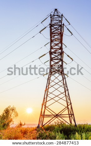 High voltage line beneath clear sky at sunset - stock photo