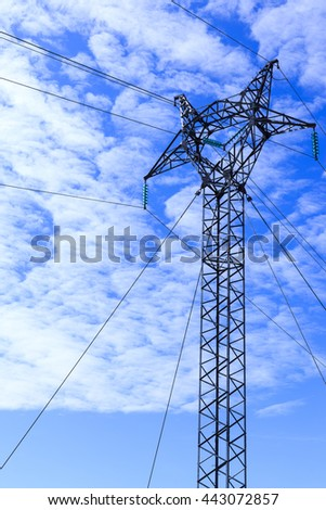 High voltage poles towering amid fresh blue sky. High voltage pole of Qaqortoq Greenland is unique hilltop stone. More pronounced in the summer each year. This high voltage pylons The city. - stock photo