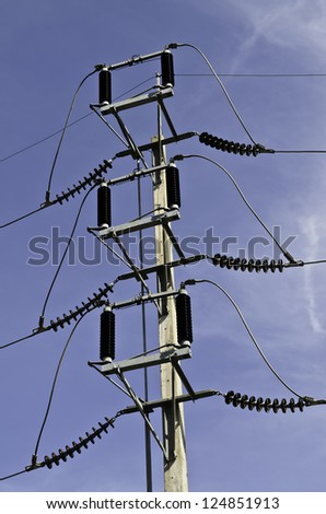 High voltage post against blue sky - stock photo