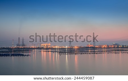 High voltage post and industry zone offshore in twilight time  - stock photo