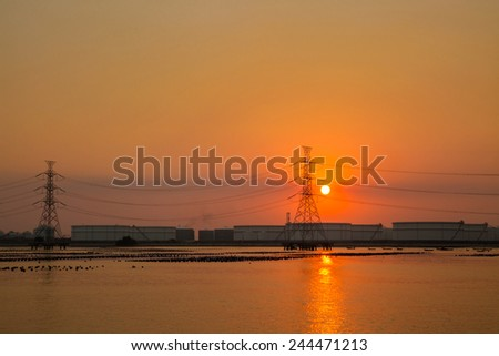 High voltage post at industry zone offshore and sea before sunset - stock photo