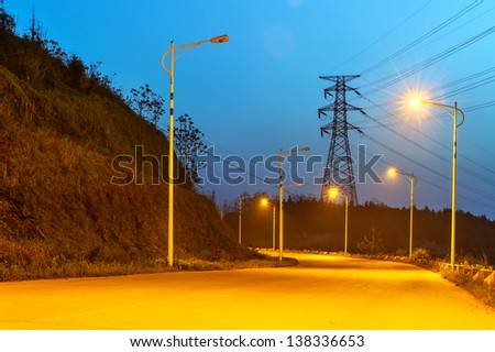 high voltage post.High-voltage tower sky background,besides the raod. - stock photo
