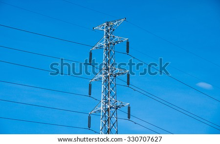 High voltage post or power transmission line tower and blue sky - stock photo