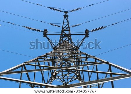 High voltage post or power transmission line tower on blue sky background - stock photo
