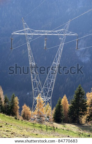 High-voltage power line flying over a meadow and a forest of larch and spruce. - stock photo