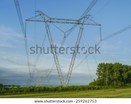 High voltage power line in green field - stock photo