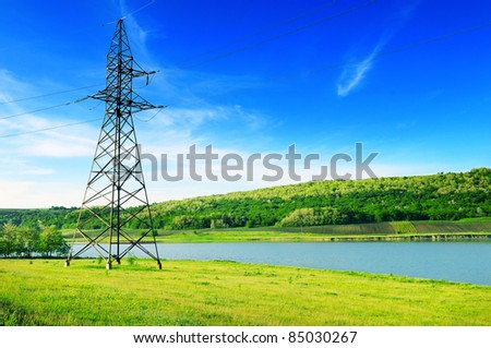 High-voltage power line on the shore of the lake. - stock photo