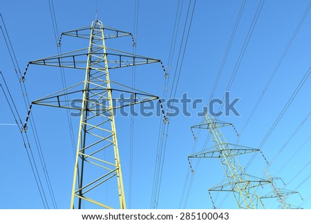 High voltage power lines against blue sky - stock photo