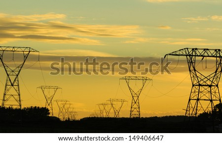 High voltage power lines in the early morning light. - stock photo