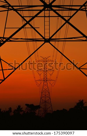 High voltage power pylons silhouettes at sunset in Thailand. - stock photo