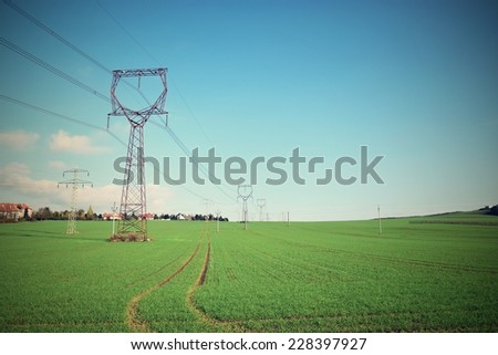 High voltage pylons on a green meadow with blue sky - stock photo
