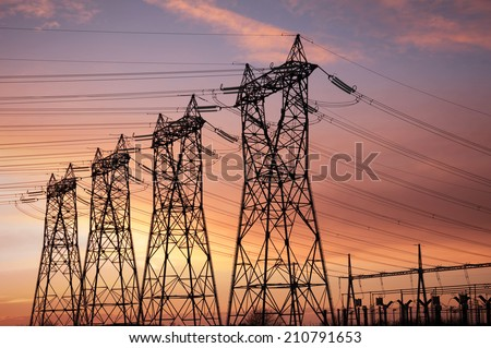 high voltage pylons silhouettes cloudy sky background - stock photo
