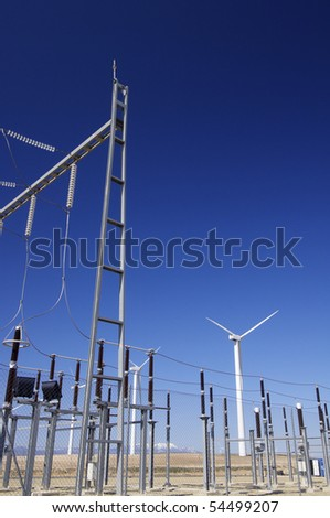 high voltage substation and windmills with blue sky - stock photo