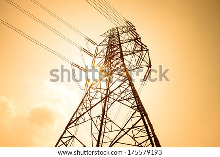 High voltage towers against the sunset background. - stock photo