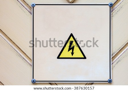 High voltage triangle sign on wooden wall. Electrical hazard sighn on wooden light yellow vintage background. - stock photo
