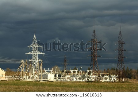 High-voltage wires and poles in the field - stock photo