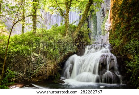 High waterfall in the mountains, surrounded by plants and forests. - stock photo