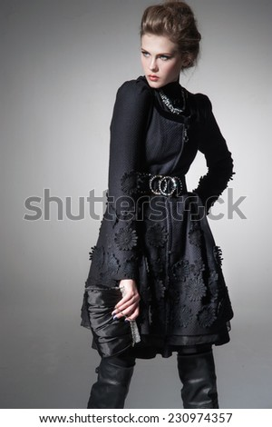 high Young fashion girl wearing elegant black clothes on gray background  - stock photo