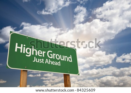 Higher Ground Green Road Sign Against Dramatic Sky, Clouds and Sunburst. - stock photo