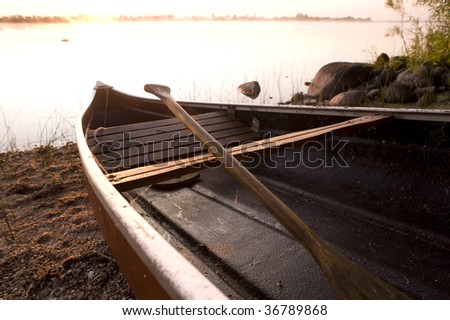 Highlight of sunrise is blown out in the background with warm old canoe and paddle in foreground. - stock photo