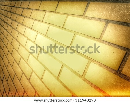 Highlighted brick wall background texture with corner vignettes viewed at an oblique angle with receding perspective - stock photo