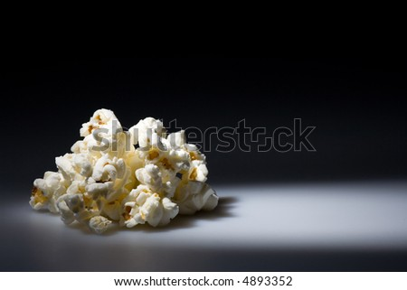 Highlighted pile of salted popcorn. Copyspace provided. - stock photo