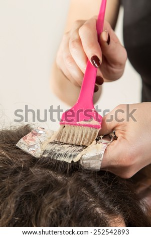 Highlighting woman client's hair in beauty parlor hairdressing salon - stock photo