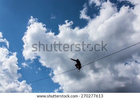 Highliner sitting on one knee on the tight rope on vibrant blue sky background, trying to stand up and go - stock photo