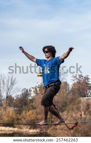 Highliner walking confidently on tightrope - stock photo