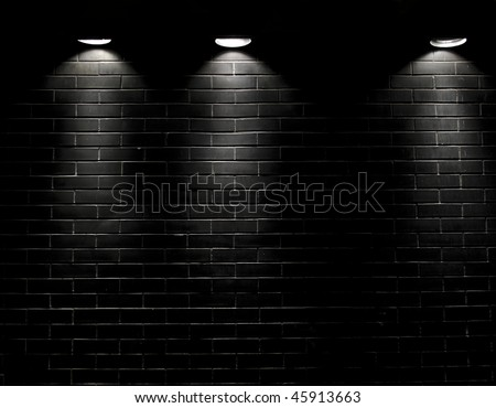 Highly contrasted spotlights on an outdoor black brick wall - stock photo