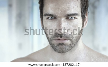 Highly detailed portrait of good looking man with wet face - stock photo