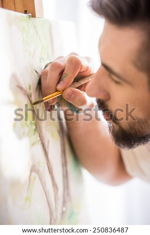 Highly gifted painter is holding brush and palette in his hand is finishing his picture. Close-up. - stock photo