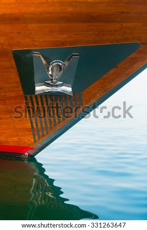 Highly polished, stainless steel anchor and plate, mounted to the wooden hull of a luxury yacht at the bow. - stock photo