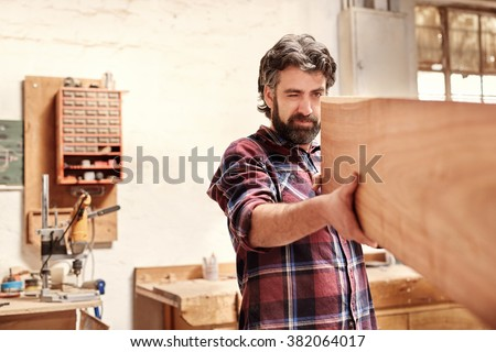 Highly skilled craftsman looking down the length of a wooden plank with one eye closed, checking for straightness and quality, in his workshop - stock photo