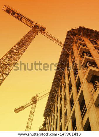 Highrise building under construction and two jib cranes over sunrising sky - stock photo