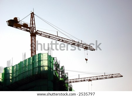 Highrise Construction -- with two cranes seen in outline and scaffolding - stock photo