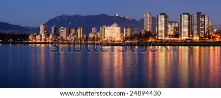 Highrises glow in gathering dusk on a winter Vancouver evening by the English Bay against a backdrop of majestic mountains. - stock photo