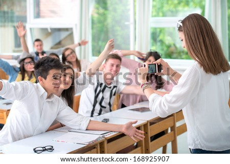 Highschool girl taking a picture of classroom with mobile phone - stock photo