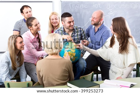 Highschool students having fun with a globe at geography class during a break in a classroom - stock photo