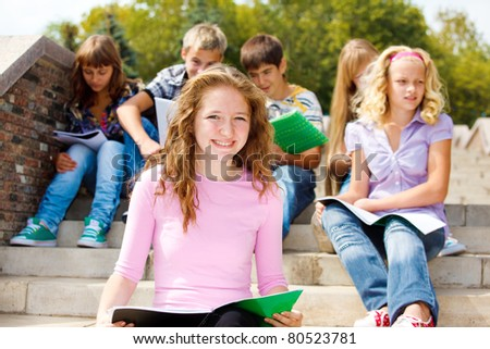 Highschool students with books, sitting on the stairs - stock photo