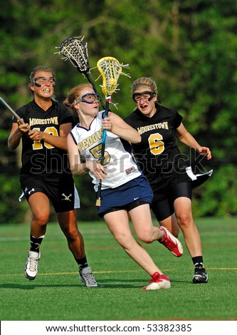 HIGHTSTOWN, NJ - MAY 13: Members of the #2 Nationally ranked Moorestown High School girl's lacrosse team battle with competitors from the Peddie School in a game on May 13, 2010 in Hightstown, NJ - stock photo