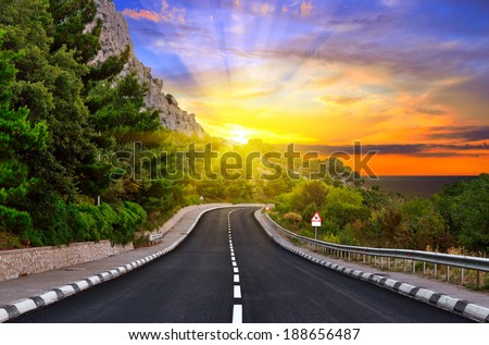 Highway against mountains and a dramatic sunset - stock photo