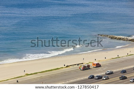 Highway along the coastline including a fire engine and paramedic vehicle park in an empty parking lot. Logos have been removed. - stock photo